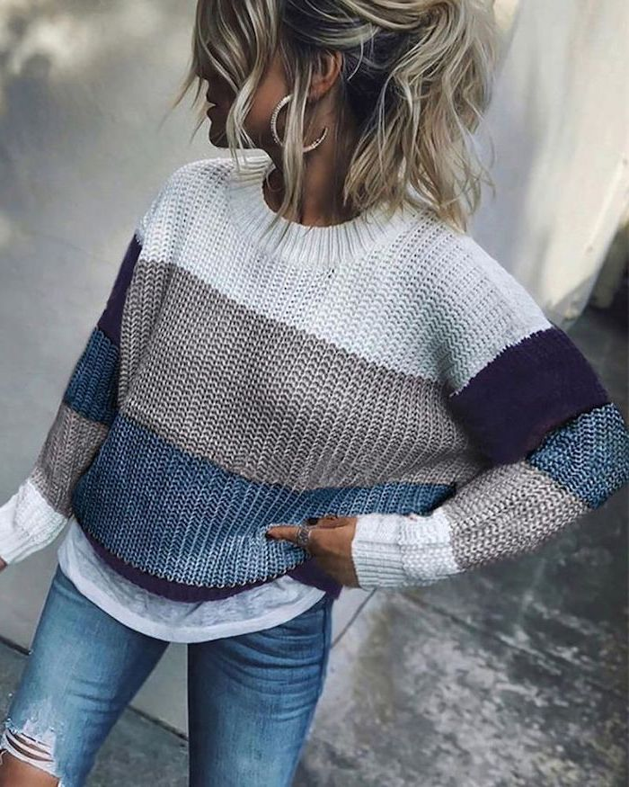 woman with blonde balayage hair in a ponytail, wearing a striped sweater and jeans, short to mid length hairstyles