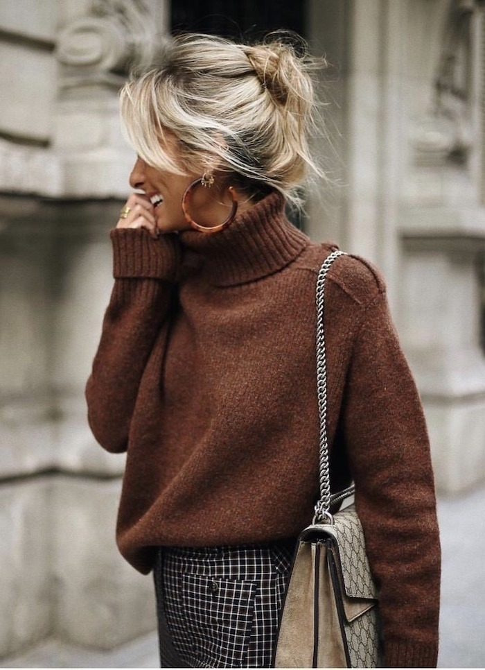 woman smiling, walking down the street, wearing brown sweater, blonde hair in a messy bun, collarbone length hair