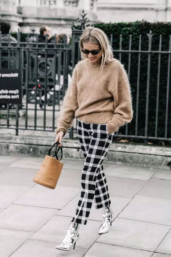 woman walking down the street, wearing beige sweater, black and white pants, silver boots, collarbone length hair, blonde hair