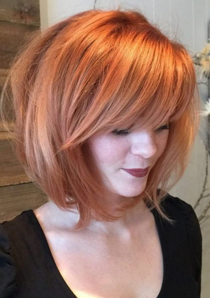 woman with red hair, asymmetrical bob with side swept bangs, wearing black top, medium hairstyles 2019