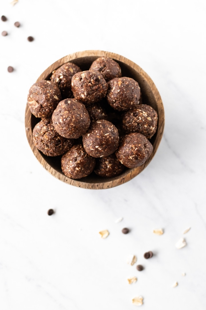chocolate truffles, with nuts, in a wooden bowl, energy balls recipe, marble countertop