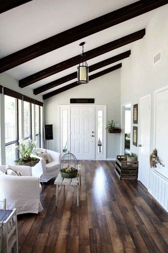 wooden floor, vaulted vs cathedral ceiling, white armchairs, white ceiling, black wooden beams, entry door