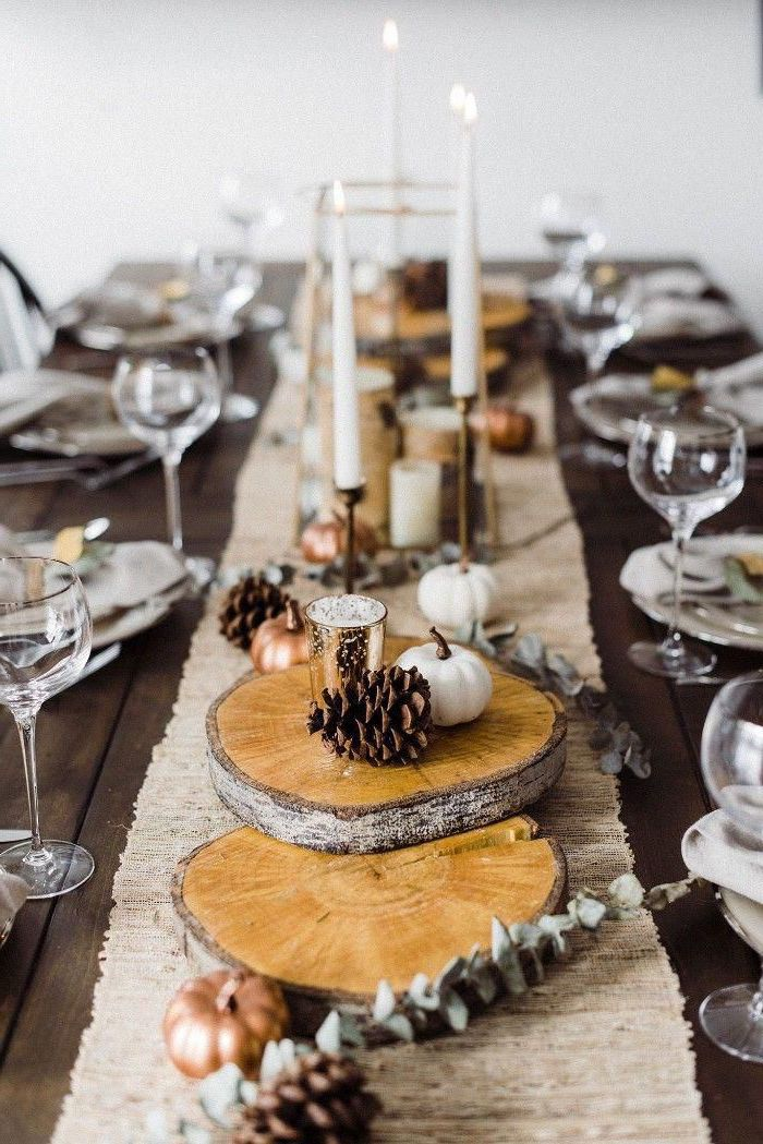 wooden logs, pine cones, pumpkins and candles on them, happy thanksgiving sign, table runner, wine glasses