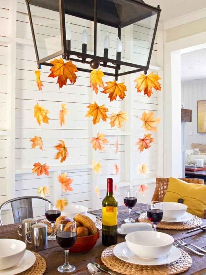 turkey decorations for thanksgiving, fall leaves, hanging from the lamp, plate settings, wine glasses, wine bottle, on the table