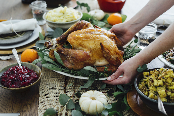 serving roasted turkey, with fresh herbs, on the side, cranberry sauce, how to make a turkey for thanksgiving, wooden table
