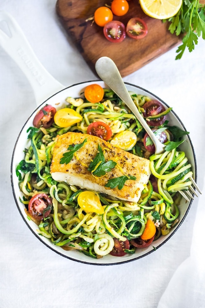 zucchini noodles, cherry tomatoes, fish fillet, foods to avoid to lose weight, white bowl, white table