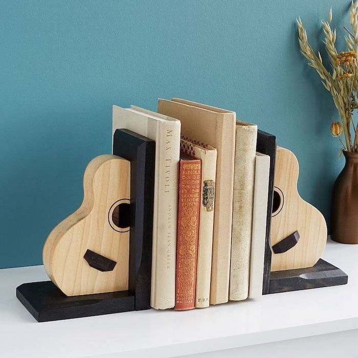 acoustic guitar bookends, christmas gift ideas for him, books in between them, placed on white surface, blue wall background