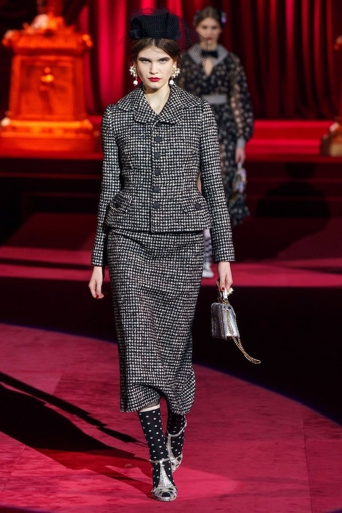 model walking on a red velvet carpet, wearing a black and white suit with skirt, current fashion trends, black hat