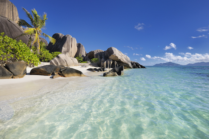 beautiful beaches, anse source d'argent beach on the seychelles, turquoise clear water, palm trees and rocks on the white sand