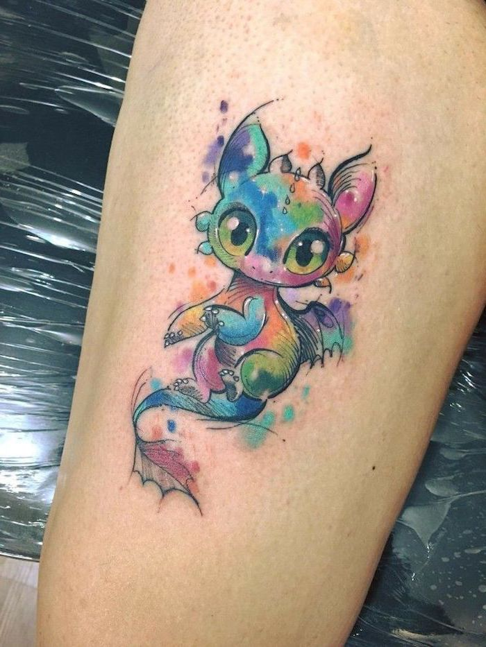 watercolor baby toothless tattoo, thigh tattoo, japanese dragon tattoo, leg leaning on black leather chair