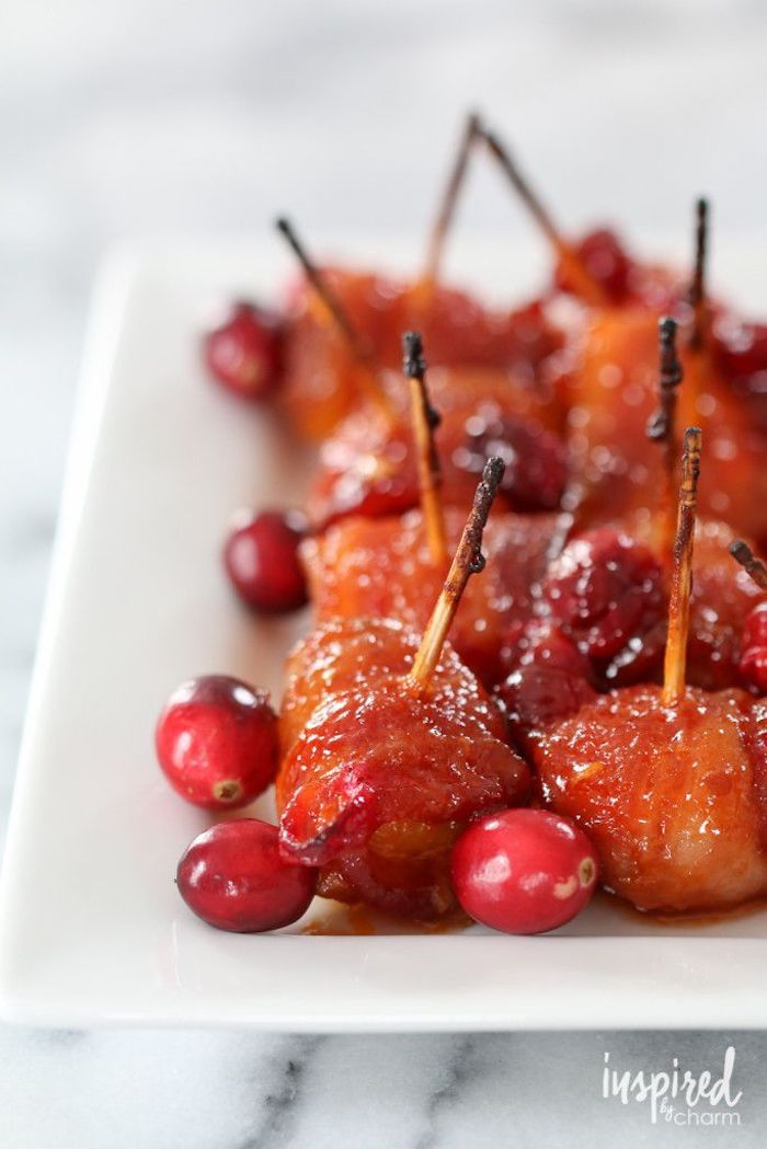 bacon wrapped chestnuts, placed on white plate, fresh cranberries on the side, christmas appetizers