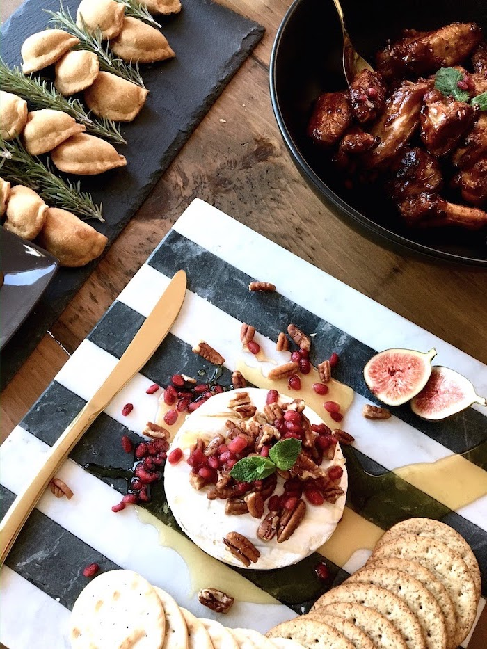 best appetizer to bring to a party, black and white board, baked brie with honey and cranberries and walnuts, crackers on the side