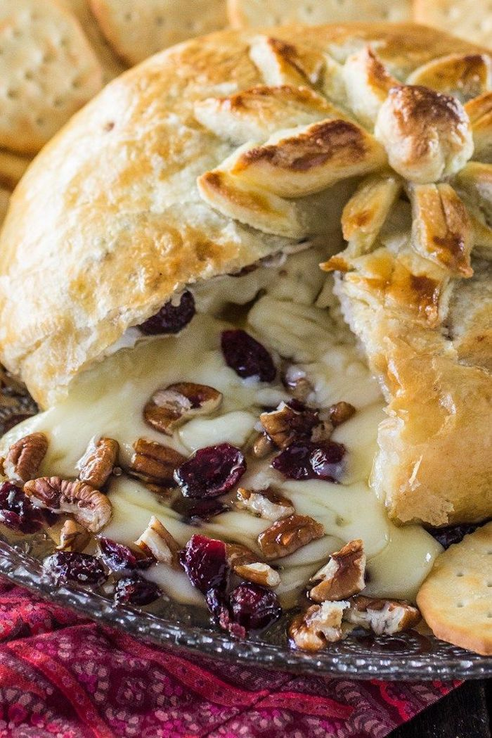 baked dough with brie cheese inside, dried cranberries and chopped walnuts, finger foods for party, crackers on the side