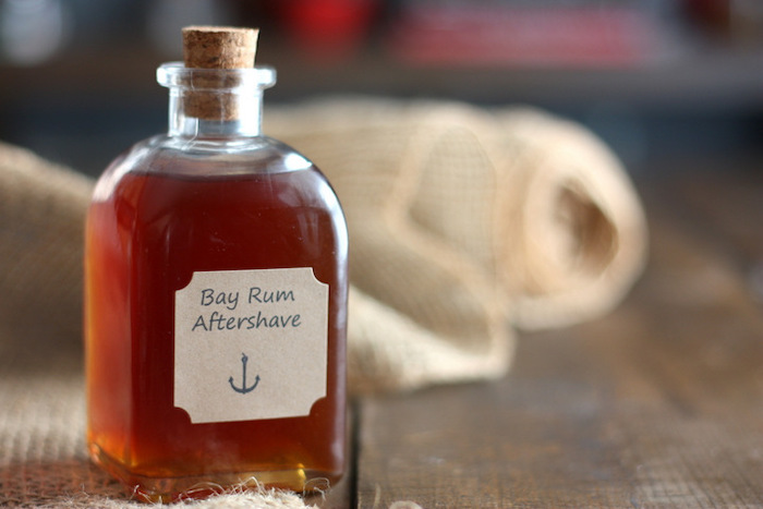 bay rum aftershave in small bottle with cork cap, step by step diy tutorial, christmas gifts for boyfriend, placed on wooden surface