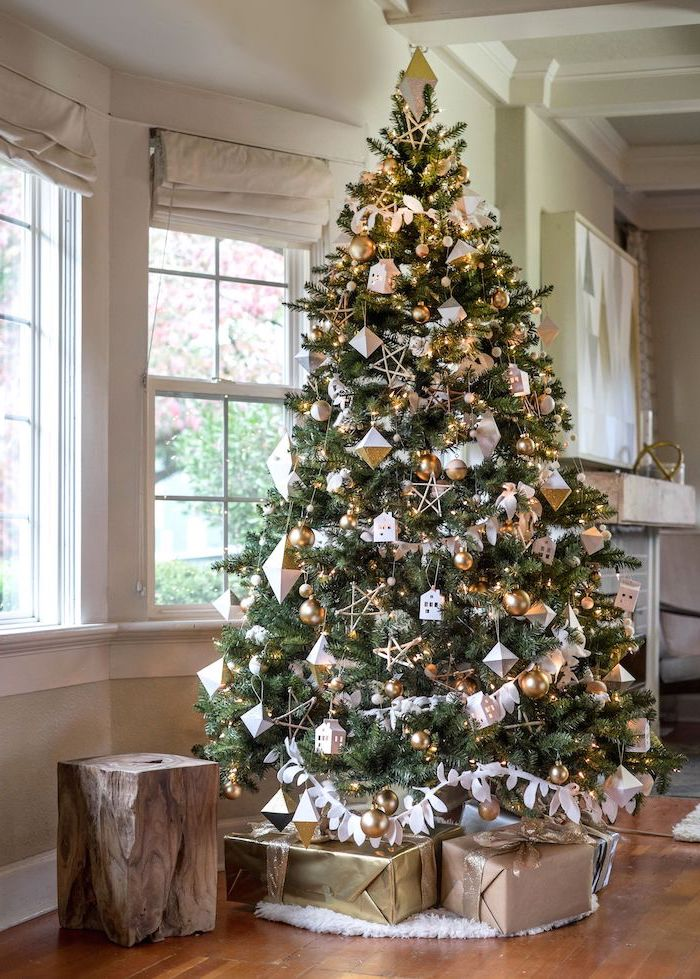tall tree decorated with gold and silver ornaments, presents underneath on white rug, how to decorate a christmas tree