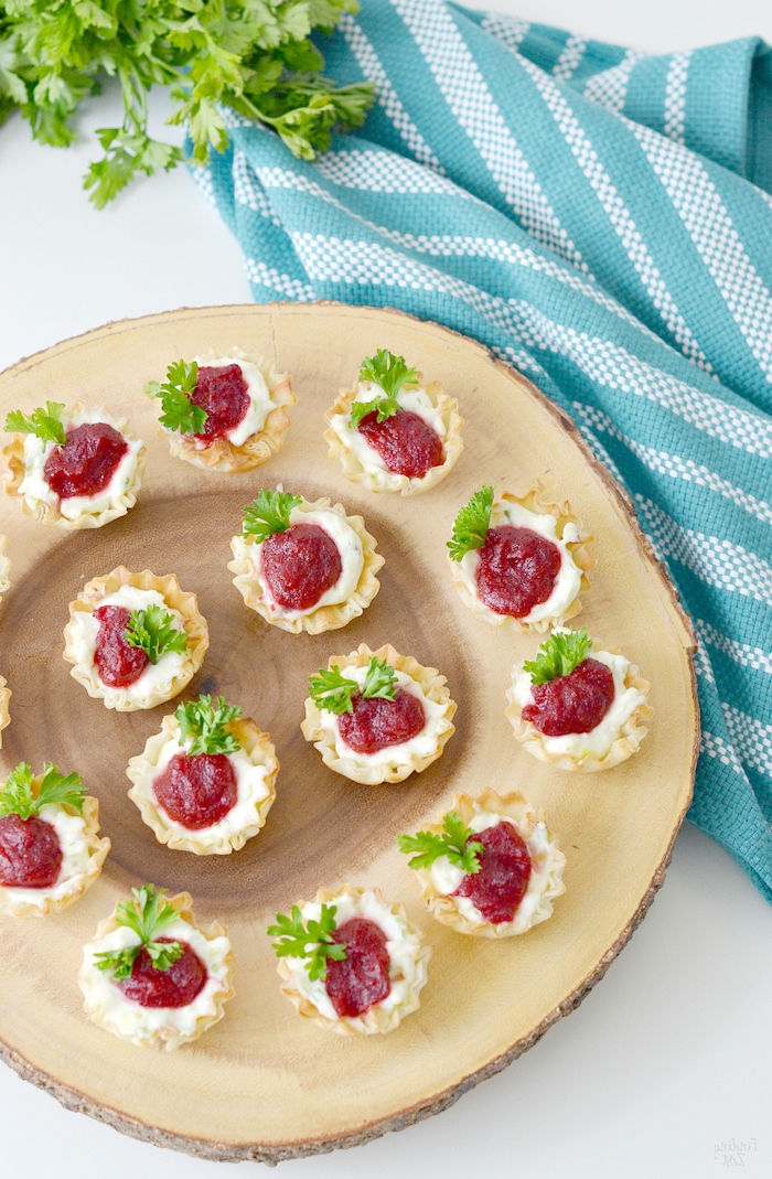 shells filled with cheese and cranberry jam, best appetizer to bring to a party, arranged on wooden board, next to blue cloth