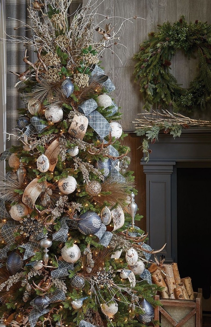 decorated tree next to the fireplace, christmas tree decorating ideas, blue and silver ornaments with blue and gold ribbons