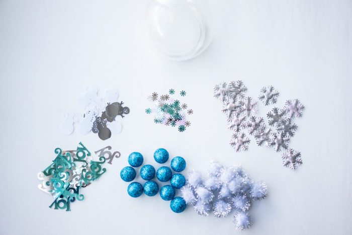blue and silver pompoms, christmas ornament crafts, silver snowflakes, placed on white surface, step by step diy tutorial