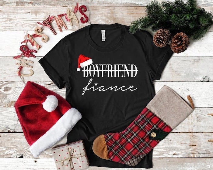 boyfriend fiance black t shirt, placed on wooden table, gifts for boyfriend, christmas hat and stocking next to it