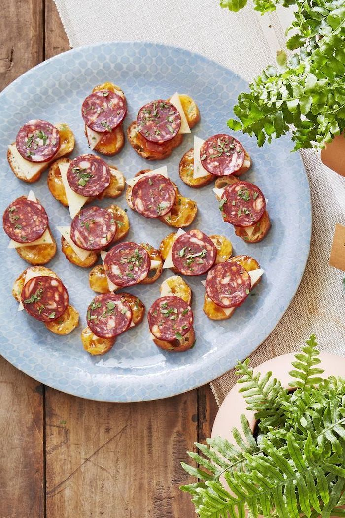 bruschetta with chorizo and cheese, arranged on blue plate, best appetizer to bring to a party, placed on wooden surface