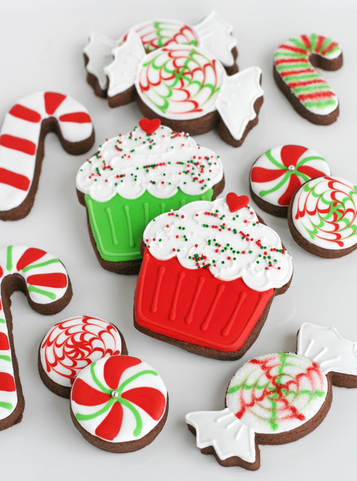 cookies in the shapes of candy canes and cupcakes, cookie decorating icing, colorful red white and green icing on top
