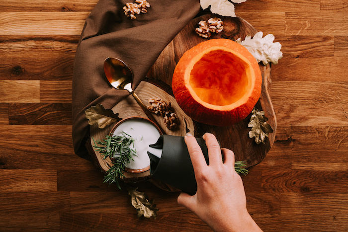 carved pumpkin, jug of milk, wooden board, fall leaves, arranged on wooden table, easy soup recipes, brown table cloth