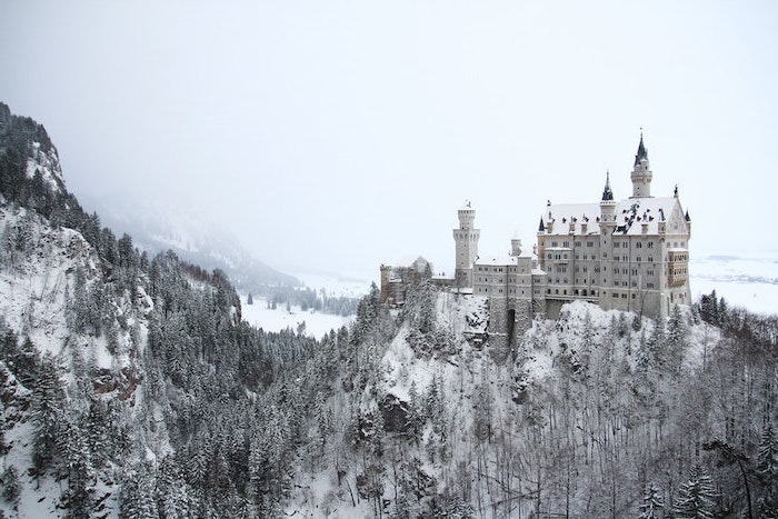 castle on a hill, surrounded by hills and tall trees, covered with snow, winter background, fog looming over it