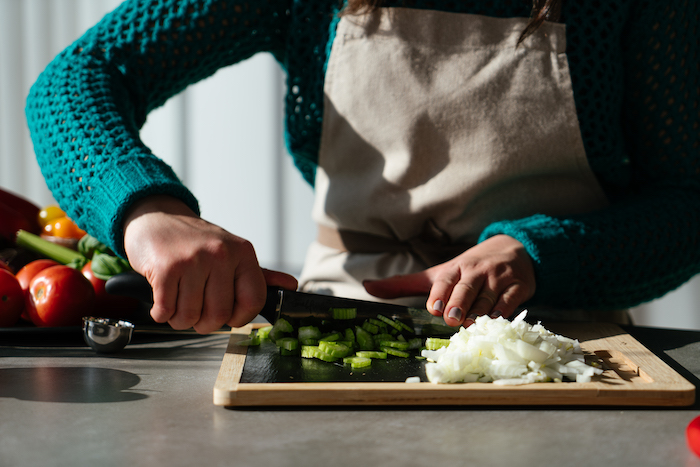 tomato soup recipe, celery and onion being chopped up with knife, on wooden cutting board, placed on grey countertop
