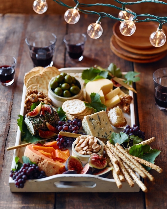 cheese board with olives grapes, different types of crackers and pretzels, christmas appetizer ideas, wooden table