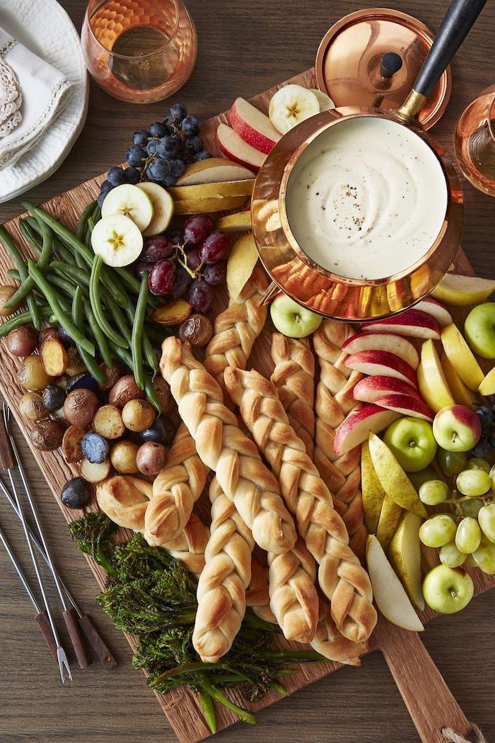 easy christmas appetizers, large wooden board, bread fruits and vegetables on it, cheese fondue in a brass bowl