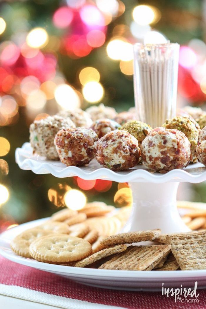 cheese truffles covered with chopped nuts, arranged on white plate, finger foods for party, different types of crackers