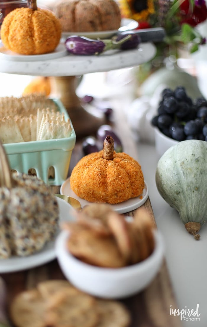 cheeseballs in the shape of pumpkins, placed on white plates, easy christmas appetizers, surrounded by different bowls