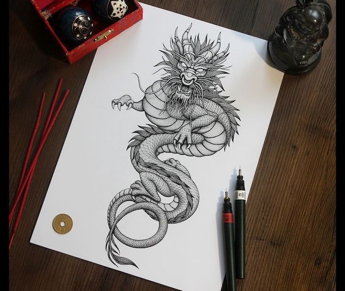 wooden table, black and white pencil sketch on it, red dragon tattoo, scary large dragon drawing