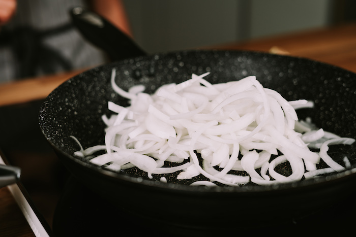 chopped onion cooking in a black skillet, placed on a hot plate, creamy soup recipes, blurred background