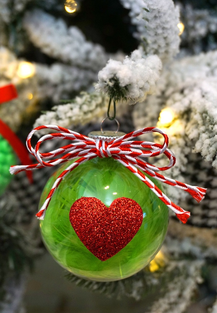 plastic bauble, filled with green feathers, easy christmas crafts for kids, red glittery heart in the front, red and white bow on top