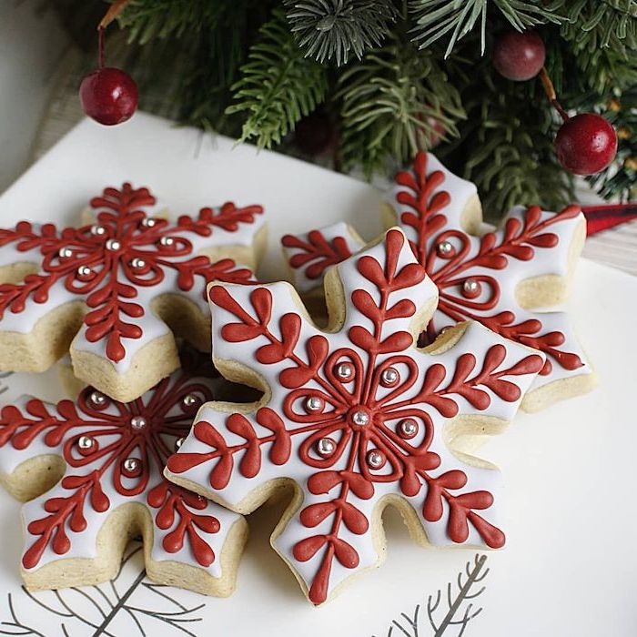 snowflake shaped cookies, with red and white icing, christmas cookie icing, placed on white plate, silver sugar pearls on top
