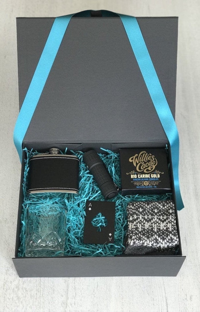 luxurious box with blue ribbons and paper inside, cute gifts for boyfriend, flask whiskey glass and deck of cards inside