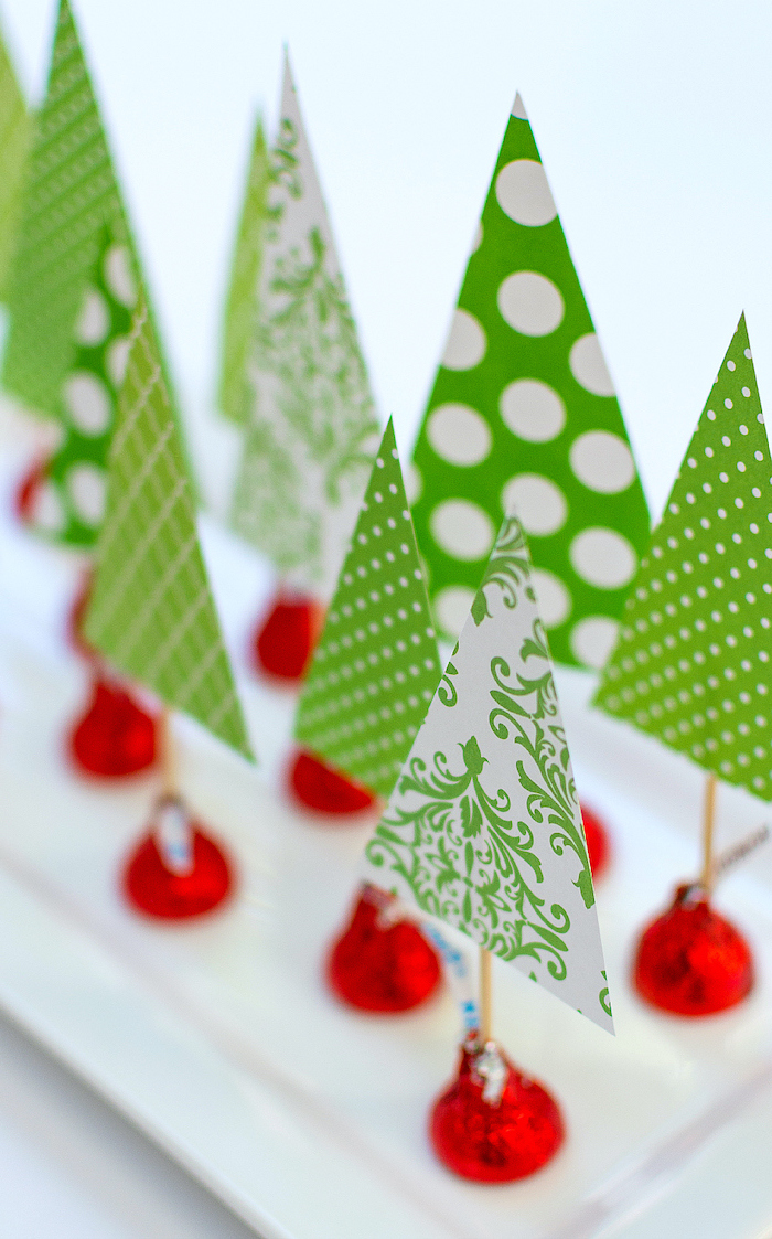 easy christmas crafts for kids, christmas trees, made of green paper and hershey's kisses, placed on white plate