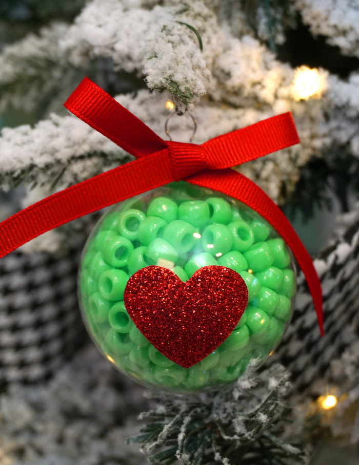 plastic bauble filled with green beads, easy christmas crafts for kids, red bow on top, glittery red heart at the front