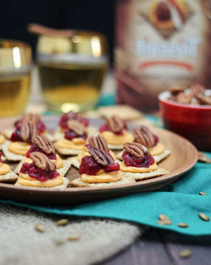 crackers with sweet potato puree, cranberry sauce and walnuts, easy party snacks, arranged on wooden plate