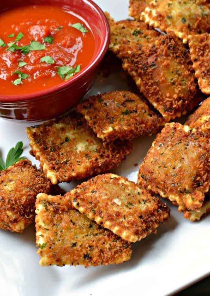 toasted ravioli, arranged on white plate, next to a ceramic bowl filled with tomato sauce, easy appetizers finger foods, parsley garnish