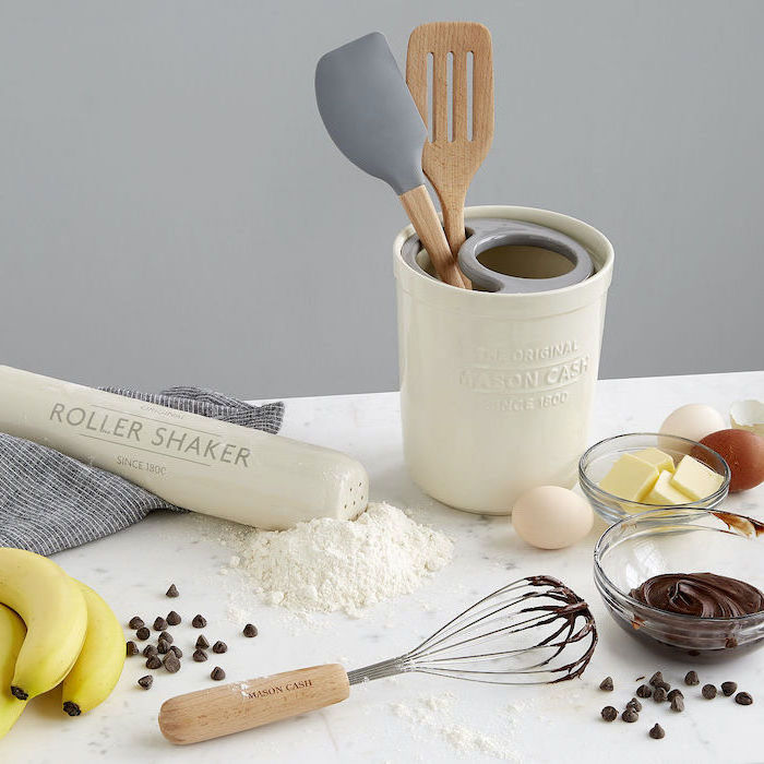 wooden set of baking utensils, personalised gifts for mom, bowls of butter and chocolate, bananas and eggs on the table