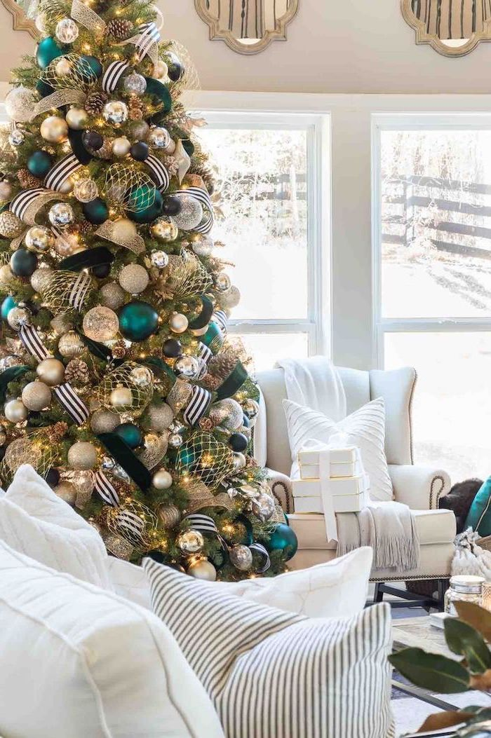 tall tree with black white and gold ribbons, turquoise silver and gold ornaments, christmas tree ribbon, next to white living room furniture