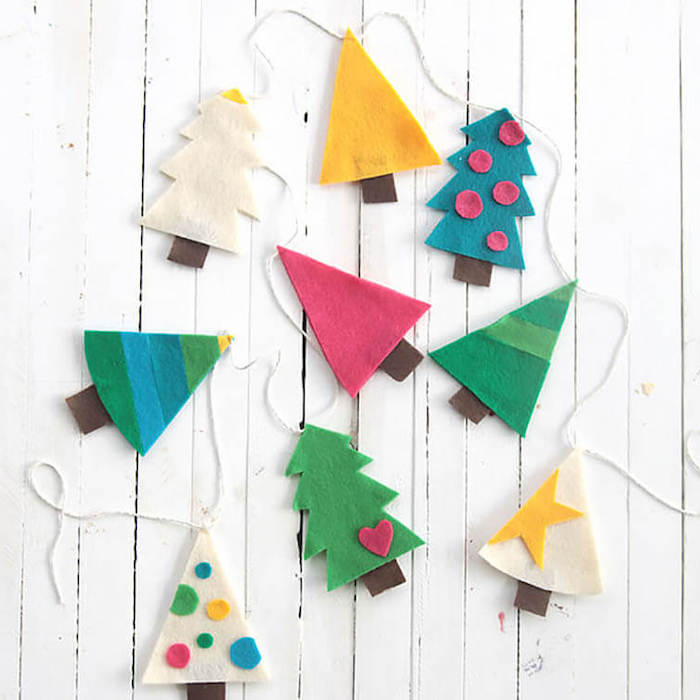 garland with christmas trees made of felt, preschool christmas crafts, placed on white wooden surface