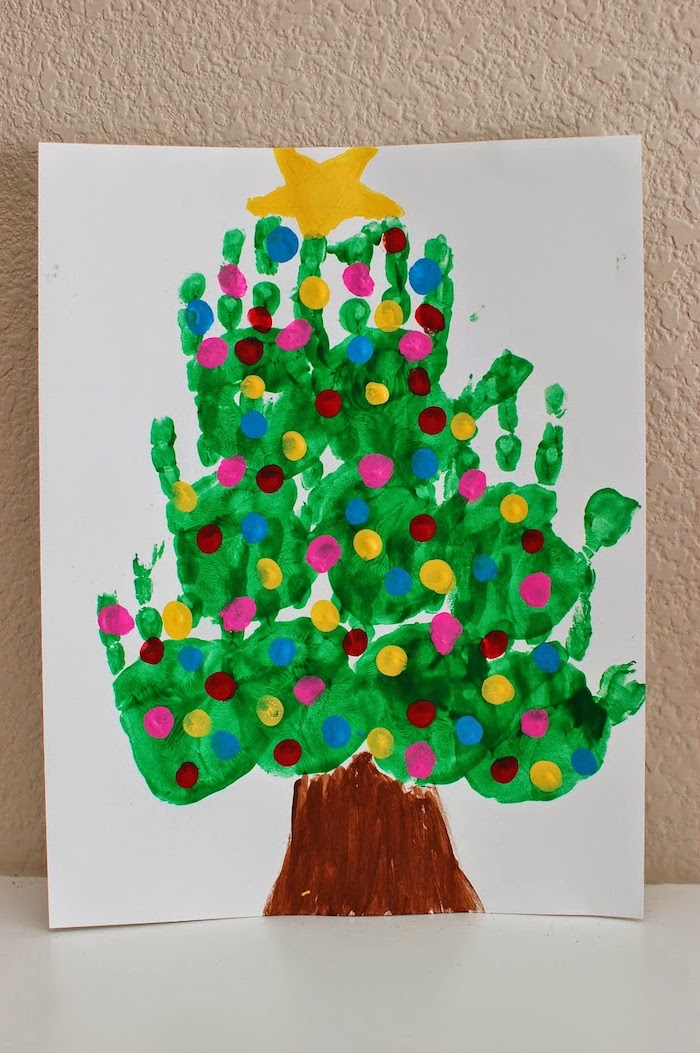 christmas tree made of handprints, painted on white paper, leaning on white wall, christmas ornaments for kids