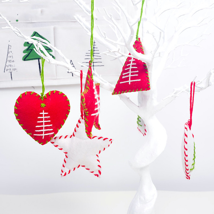 christmas tree ornaments made of felt, hanging on a ceramic white tree, christmas crafts for kids, red and white with green stitches