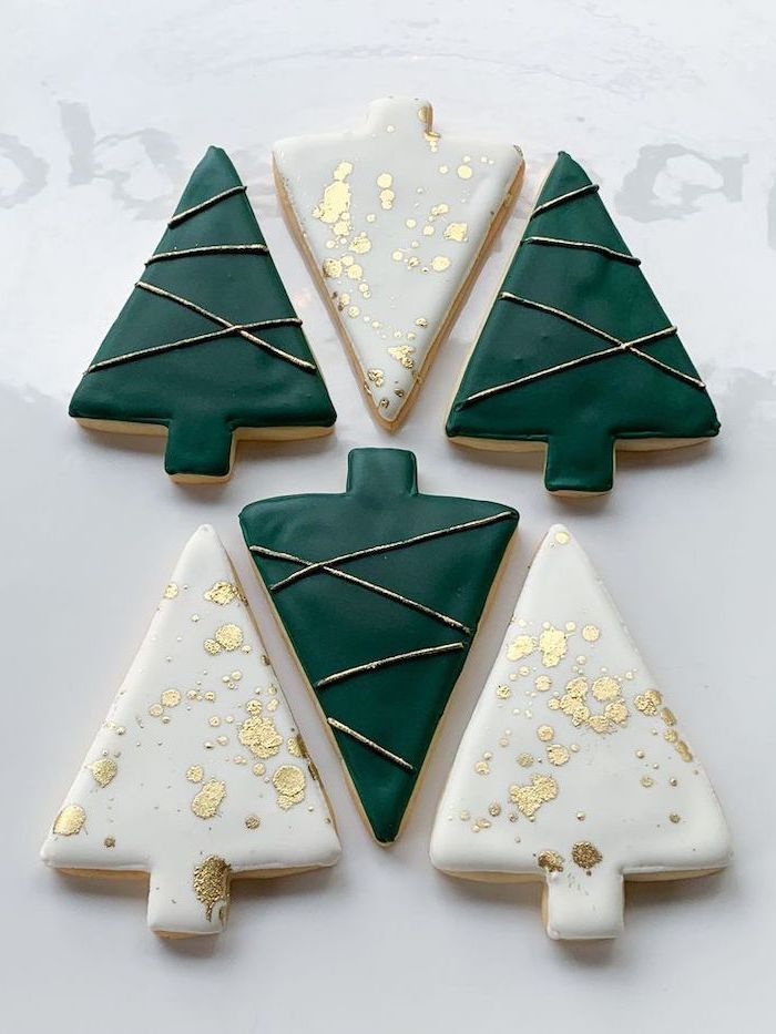 christmas tree shaped cookies, green white and gold icing on top, cookie icing, placed on white surface