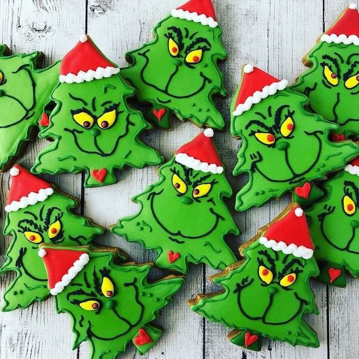 christmas tree shaped cookies, face of the grinch on them, decorated with green icing, decorated sugar cookies
