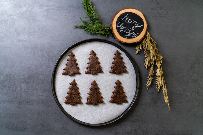 six christmas tree shaped cookies, placed on paper lined baking sheet, vegan gingerbread cookies, placed on grey surface