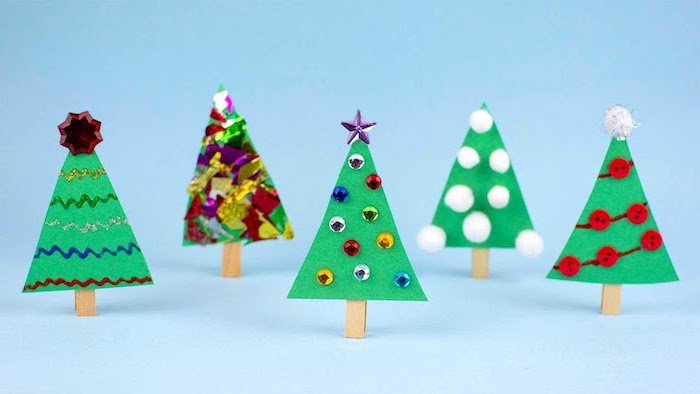 christmas activities for preschoolers, christmas trees made of felt, pompoms and colorful confetti, placed on blue surface